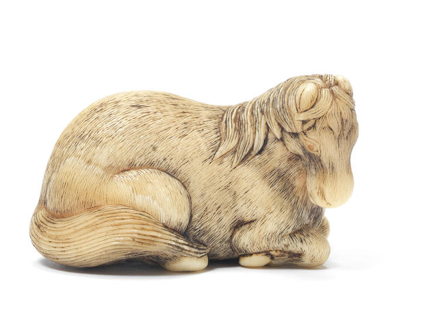 An ivory netsuke of a recumbent stallion By Okakoto, Kyoto, early 19th century