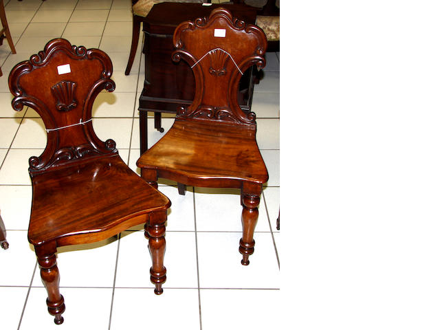 A pair of Victorian carved mahogany hall chairs,