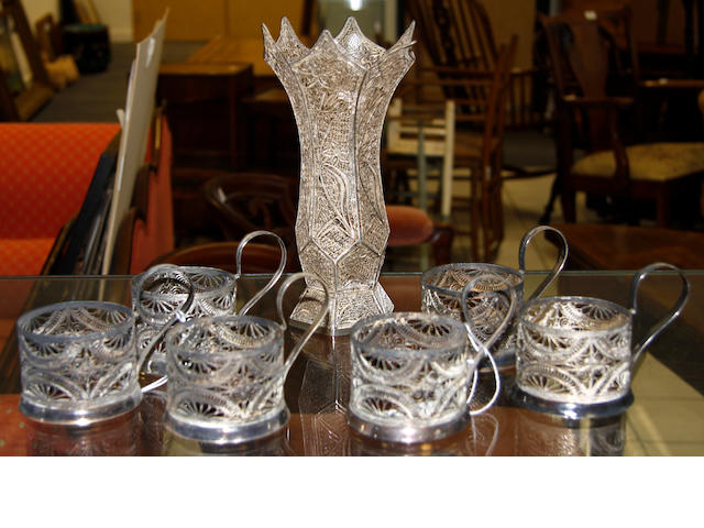 A set of six silver coloured filigree cup holders,