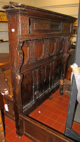 A panelled and carved oak double bedstead,