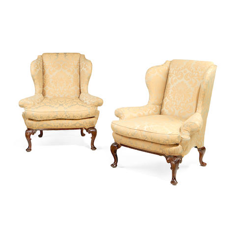 A pair of second quarter 20th century stained beech wingback armchairs in the George II style