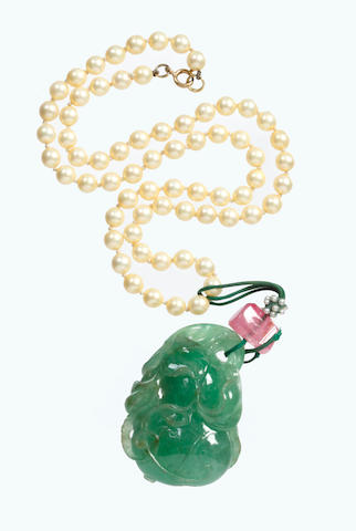 A green stone or quartz pendant hung on a beaded necklace