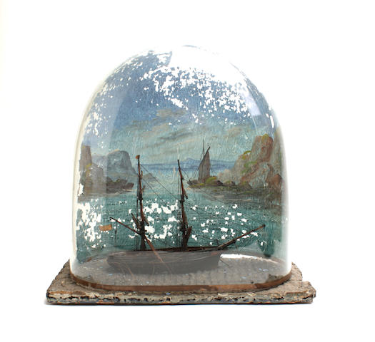 A model of a twin masted sailing ship in a painted glass dome 33cm wide, 19cm deep, 34cm high.