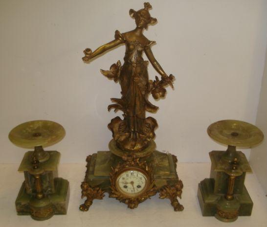 An early 20th Century French gilt metal and onyx mantle clock, the 9cm dial with Arabic chapter, 8 day movement striking on a bell, the case surmounted by on Art Nouveau style figure, 60cm, key and pendulum, together with a pair of associated mantelpiece vases. (3)