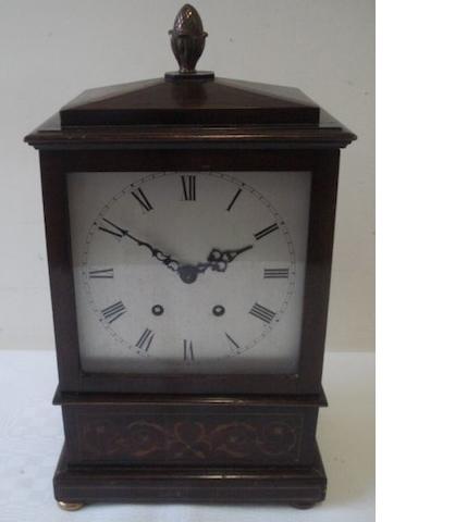 "A late 19th Century inlaid mahogany bracket clock, in the Regency style, the 6.5"" silvered dial with Roman chapter French 8 day movement raised on brass bun feet and side ring handles, and later cone finial, overall 39cm high, pendulum."