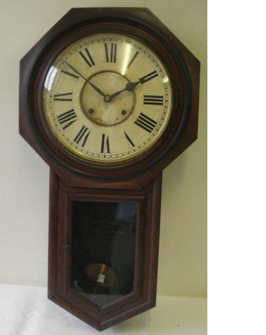 An early 20th Century wall clock, by Ansonia Clock Co, the circular dial with Roman chapter, octagonal frame and visible pendulum glazed door, 80cm.