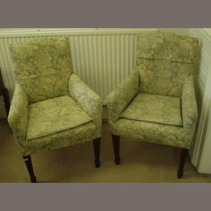 A pair of good quality Edwardian upholstered armchairs, the shaped backs and outswept arms with William Morris style printed cotton loose covers, on inlaid mahogany tapered legs and spade feet, 97cm high.