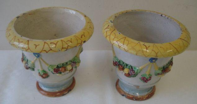 A pair of 19th Century glazed Majolica urns, in Della Robbia style, the circular with out-turned rim, the body moulded with fruit and floral swags, circular pedestal foot, 24cm.