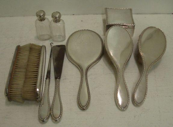 An Edwardian silver mounted ten piece dressing table set, William Comyns, 1903/04, with bell-flower borders comprising:- a square jewel box, with concave sides, the hinged cover enclosing a velvet lined interior, hand mirror, pair of hair and clothes brushes, button hook and shoe horn, pair of mounted glass toilet water bottles.