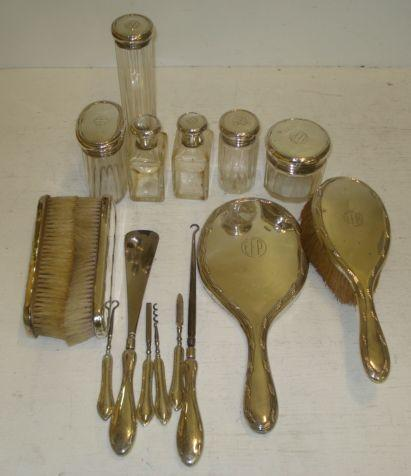 A George V silver mounted sixteen piece dressing table set,Drew & Sons, 1916/17, with leaf tied threaded edges and initialled 'E.F.P', comprising six mounted facet cut glass bottles and jars, hand mirror, pair of clothes brushes, hair brush, mounted steel button hook and shoe horn and manicure tools.
