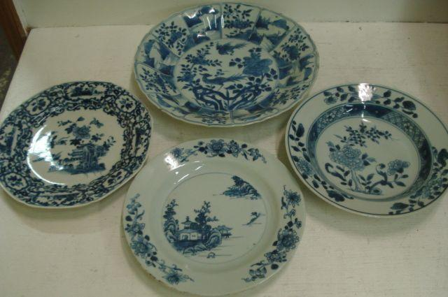 A Chinese blue and white plate, centrally painted with birds amongst flowering branches, enclosed by a shaped border with alternating panels of flowers and water landscapes, 28.5cm and three other Chinese blue and white plates. (4)