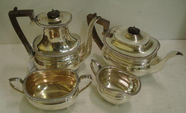 A Regency style four piece silver tea and coffee service, Goldsmiths & Silversmiths Company, 1916/17, of oval form with gadroon borders, the tea and coffee pots with wooden harp handle and finial, on ball feet, 57ozs, crested.