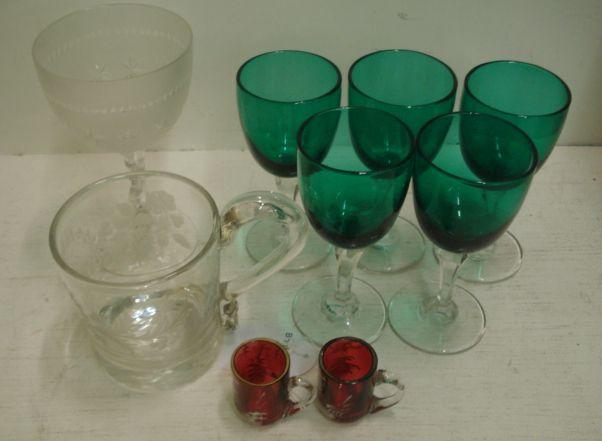 A pair of miniature Mary Gregory style cranberry glass mugs, enamelled with a young boy in a landscape, 41cm, and a set of five drinking glasses with 'Bristol' green bowls and other glasswares.