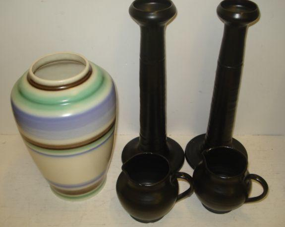 A Poole Pottery vase, circa 1930, of tapering circular form, decorated with shaded bands, of blue, green and brown, 25.5cm, together with a pair of Carter Stabler Adams Poole pillar candlesticks with incised line decoration in a satin black glaze, 32cm and pair of similar glazed jugs, 10cm, all with impressed marks. (5)
