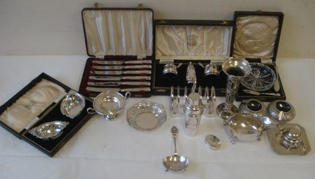 A quantity of silver wares to include:- a six division toast rack, Sheffield 1933, small sauce boat with cut card rim on three shell capped hoof feet, 1931, a spill vase with green glass liner, 1910, two cedar lined cigarette boxes, square ashtray with engine turned border, two bon bon dishes, mustard pot, tea strainer, a cased three piece panelled cruet, Birmingham 1952, cased cut glass butter dish with two butter knives, a cased pair of silver bon bon dishes, cased set of six silver handled tea knives, two Middle Eastern ashtrays, and a novelty plated cocktail stick holder in the form of a cocktail shaker.
