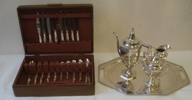 An American sterling part canteen of cutlery, each piece with flower cast handle, comprising:- 2 serving spoons; 8 dessert spoons; 8 teaspoons; 8 dinner forks; 8 dessert forks; straining spoon; 8 hollow handle dinner knives ; 50ozs total approximately, together with a three piece silver plated coffee set on a two handled tray.