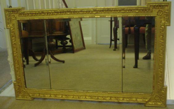 A 20th Century landscape mirror, in early 18th Century style, the three bevelled plates contained in a gilt gesso fame with projecting corners with acanthus leaf and flower head, 59 x 96cm.