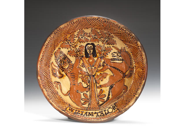 A Staffordshire slipware dish by William Talor, circa 1680-85, Depicting Charles II in the Royal Oak, the head of the king within the leafy branches, flanked by a lion and unicorn, the trellis border including the name of the potter WILLIAM TALOR (A crack runs from the rim at 1 o'clock extending just into the well, another crack at 7 o'clock runs sideways to beneath the tree, some rim chips)