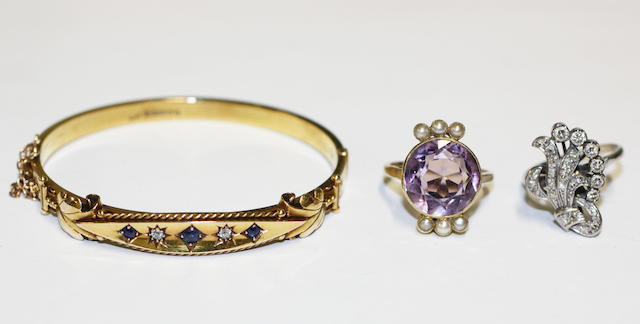 Three item of jewellery, comprising an early 20th century 15ct gold hinged bangle, set with sapphires and diamonds, a diamond dress ring of scroll design and a round-cut amethyst ring between trios of seed pearls. (3)
