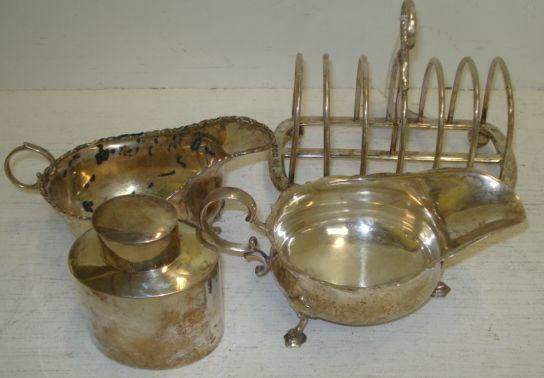 An Edwardian silver seven bar wire-work toast rack, Goldsmiths & Silversmiths Company, 1909, of heavy gauge, on ball feet, 15.5cm, a George III style oval tea caddy, Birmingham 1910, with pull-off cap, and two George III style helmet sauce boats, Sheffield 1910 & Birmingham 1910, one lacking foot, 21ozs . (4)