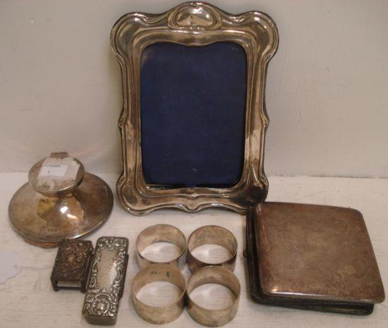 A set of four plain circular silver napkin rings, 1946, and the following silver, an Art Nouveau mounted photograph frame, William Neale, Chester 1903, of shaped outline, a capstan inkwell, Walker & Hall, Sheffield 1915, the mount for a folding bedside clock, Edwardian match box sleeve, and a late Victorian rectangular snuff box, Levi & Salaman, Birmingham 1897, with foliate embossed hinged cover. (9)