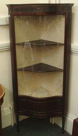 An Edwardian mahogany floor standing corner cabinet, of serpentine outline, in George III style, enclosed by a glazed door, having a fluted and rosette carved frieze, on chanelled square tapered legs, 73cm.