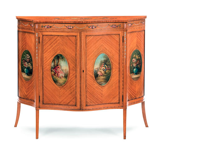 An Edwardian painted satinwood serpentine cabinet