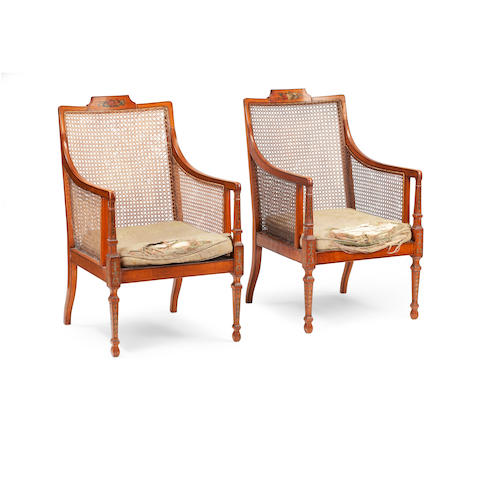 A pair of late Victorian large painted satinwood and caned bergère armchairs