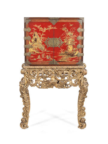 A small 18th century scarlet japanned cabinet on a carved giltwood stand
