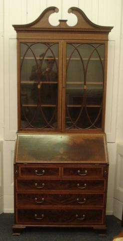 An Edwardian 'Sheraton Revival' mahogany bureau bookcase, satinwood crossbanded, boxwood and ebony strung, the upper part with a broken swan neck pediment above adjustable shelves enclosed by a pair of glazed tracery doors, centred by inlaid fan paterae, the hinged sloping fall enclosing a fitted interior, two short and three long drawers below, on ogee bracket feet, 97cm.