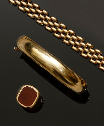 Three items of 9ct gold jewellery Comprising a plain polished hinged bangle, a brick-link chain bracelet and a cornelian signet ring. (3)
