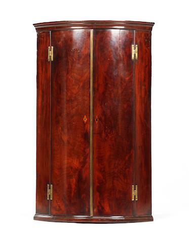 A George III mahogany bowfront corner cupboard