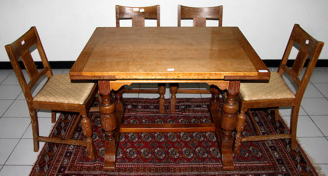 An Art Deco Waring & Gillow oak and walnut veneered dining suite,comprising a ideboard, 152cm wide, drawer leaf table and four chairs.