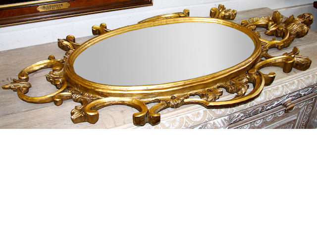 An oval carved giltwood mirror