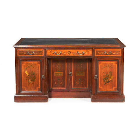 A late Victorian fiddleback mahogany, satinwood and polychrome decorated kneehole desk in the Sheraton revival style