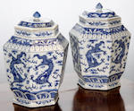A pair of Chinese blue and white hexagonal tapering jars and covers, painted with dragons chasing flaming pearls, 29cm.