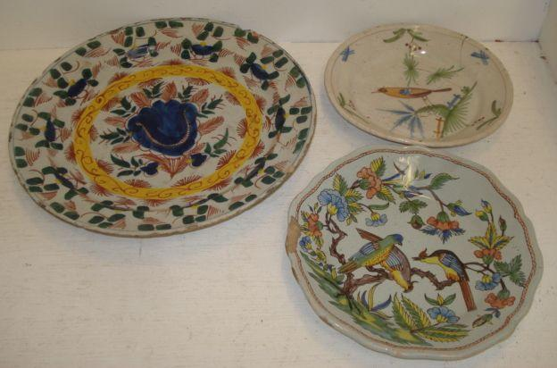 A Dutch Delft dish, 18th Century, painted with stylised flowers and leaves, 35cm, and two others painted with birds. (3)