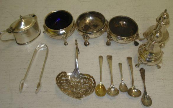 A pair of George III silver cauldron salt cellars, marks rubbed, each on three hoof feet, and the following silver, a George III style cauldron salt cellar and matching pepperette, 1916/17, a similar pepperette, 1961, a George III style oval mustard pot, two George III/IV salt spoons, and three mustard spoons, pair of Victorian sugar tongs and a continental sifter spoon, 12ozs weighable.