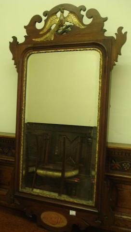 An early 20th Century mahogany wall mirror, in the George II style shaped with fret cresting with gilt bird, and inlaid shell panel, 91 x 50cm.
