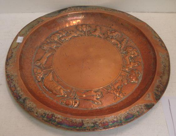 A circular copper alms dish, the sunken centre embossed with a continuous band of a hunting scene,47cm.