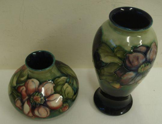 A post war Moorcroft vase, circa 1950, baluster form decorated in the Clematis pattern on a shaded blue and green vase, impressed marks, 22cm, and another squat form vase, similarly decorated, impressed marks, 12.5cm. (2)