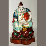 A Japanese late 19th century figure, crouching, with fish