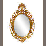 An oval carved and pierced giltwood hall mirror
