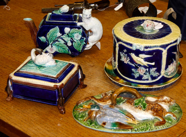 An English majolica cheese dome and stand, a teapot and cover, a sardine dish and a Minton game dish cover, late 19th century