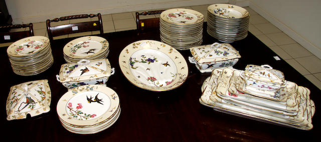 A Continental porcelain fifty eight piece part dinner service, boldly decorated with birds and flowers in a pale yellow border