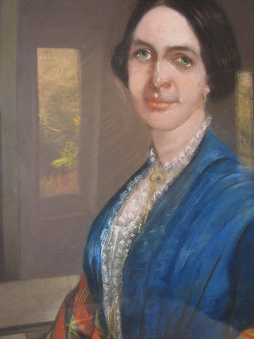 A 19th Century English School pastel portrait of a lady with black hair and blue dress.