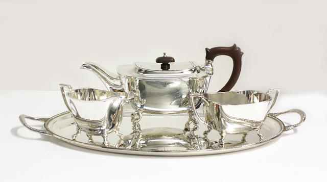 A silver three piece tea set and a twin handled tray,  (4)