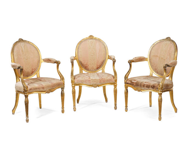 A set of three George III carved giltwood open armchairs in the manner of Thomas Chippendale