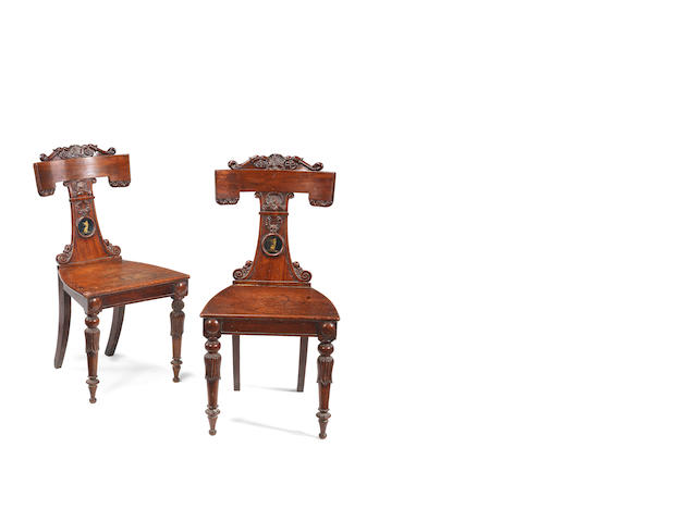 A pair of Regency carved mahogany hall chairs