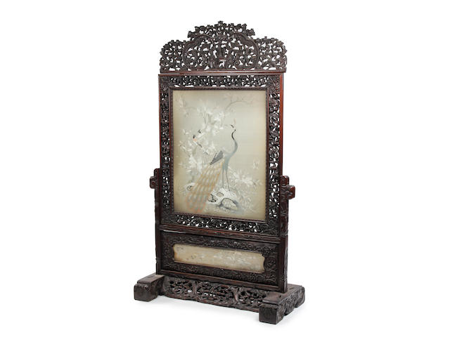 A late 19th Century carved Oriental screen on stand, with high quality silk work panel decoration